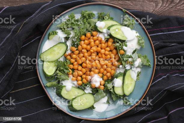 Photo of Healthy vegetarian salad with roasted chickpeas,kale, cucumber and dressing. Healthy detox eating. Vegan and vegetarian food.