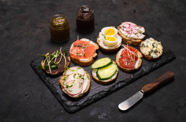 Gesunde vegetarische Sandwiches. Verschiedene Vollkorn-Gemüsebruschettas mit Mikrogrün. Essen richtiges Konzept, Essen Hintergrund. Sandwiches mit cremigem Käse, Gurken, Eiern, Lachs, Blaukäse und Mikrogrün auf Schieferplatte. – Foto