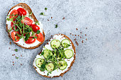 Healthy vegetarian toasts with cream cheese, cucumber, cherry tomato and micro greens on top. Table top view on concrete backdrop. Copy space