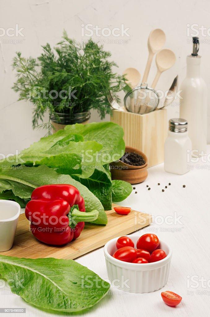Healthy vegeterian ingredients for spring fresh green salad and kitchenware in white elegant kitchen interior. Spring vitamin dieting food. stock photo