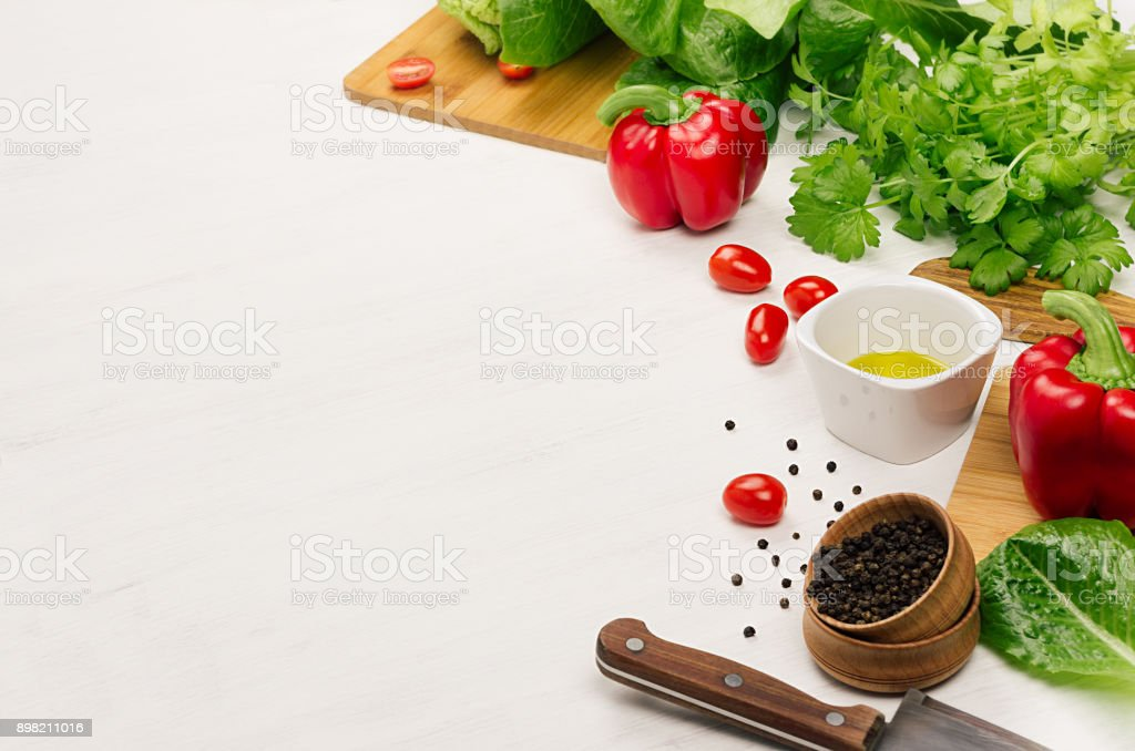 Healthy vegeterian ingredients for spring fresh green salad and kitchenware on white wood table, copy space. Spring vitamin dieting food. stock photo