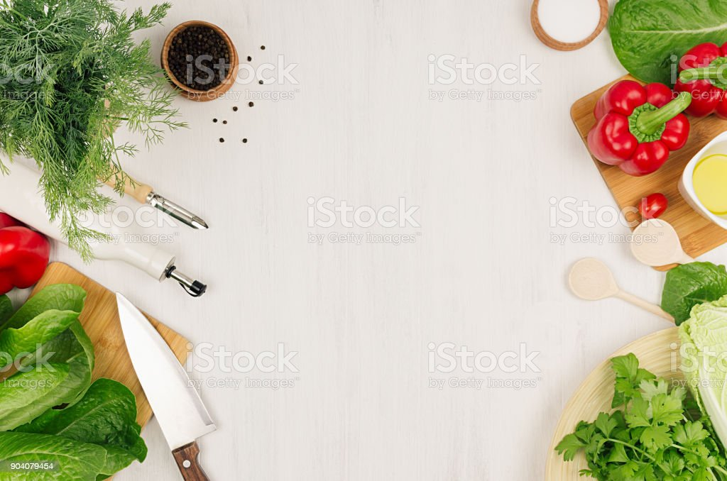 Healthy vegeterian ingredients for spring fresh green salad and kitchenware on white wood board, top view, copy space. stock photo