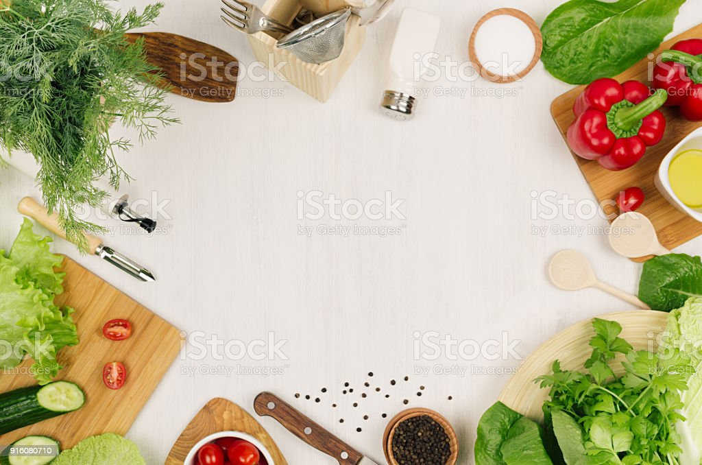 Healthy vegeterian ingredients for spring fresh green salad and kitchenware on white wood board, top view, copy space. Spring vitamin dieting food. stock photo