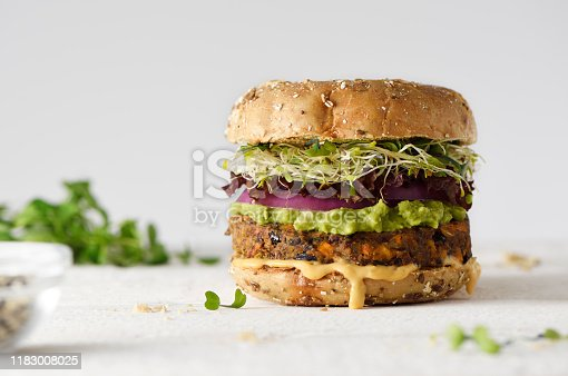 Healthy veggie burger with vegan pattie, guacamole, onion and sprout