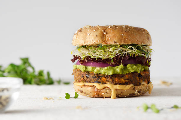Healthy veggie burger Healthy veggie burger with vegan pattie, guacamole, onion and sprout vegetarian stock pictures, royalty-free photos & images