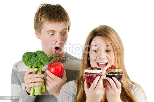 Subject: Healthy and unhealthy diet. Healthy vegetables and fruits for good health facing the challenge and temptation of junk food. Isolated on a white background.