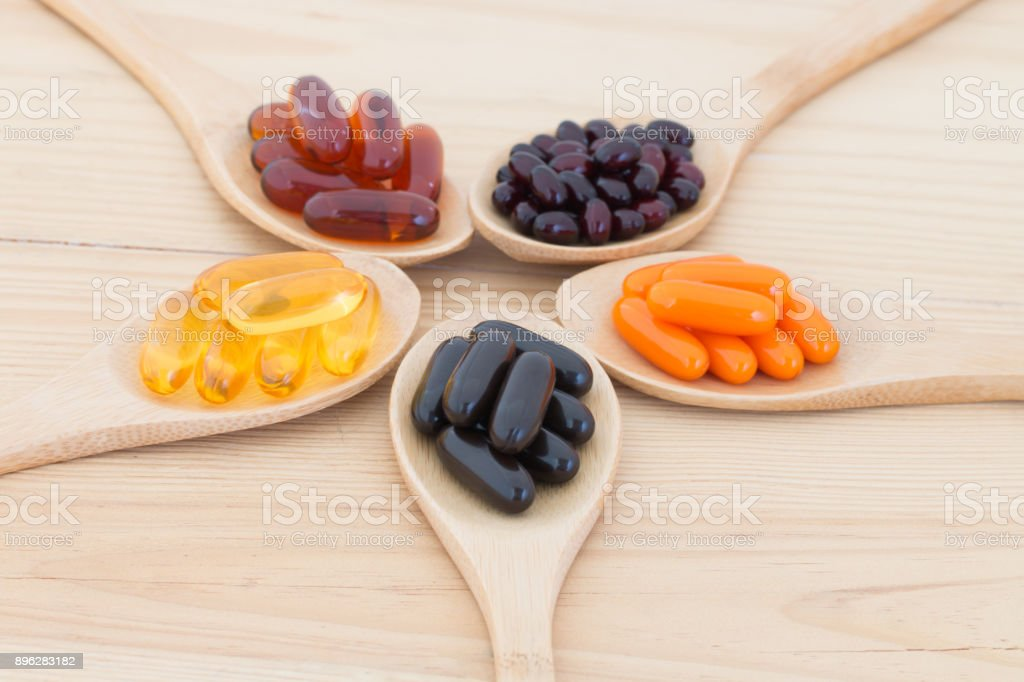 Healthy Vitamin supplement capsules in a spoons. stock photo
