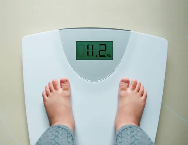 Sağlıklı kilo bebek veya çocuk kavramı, 2 yıl için eski çocuk üzerinde ağırlık ölçekleri, üstten görünüm ayakta stok fotoğrafı