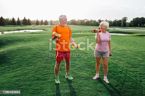 senior man and woman practice fitness exercise with dumbbells in a park at sunny day