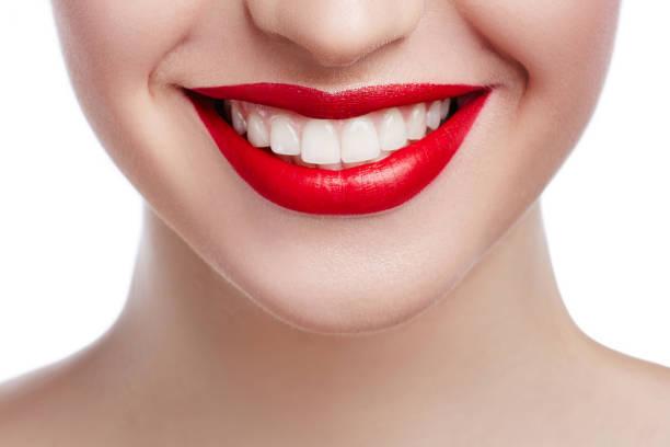 Gros sourire blanc en bonne santé. Beauté femme avec le sourire parfait, les lèvres et les dents blanches. Belle fille de modèle avec des lèvres rouges isolés sur fond blanc. Dents blanchissant et le nettoyage, les soins dentaires. - Photo