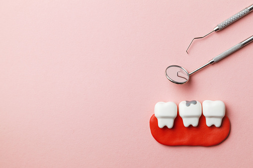 istock Healthy white teeth and tooth with caries on pink background  and dentist tools mirror, hook. Copy space for text. 1133134306