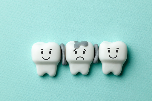 istock Healthy white teeth are smiling and tooth with caries is sad on green mint background. 1132333174