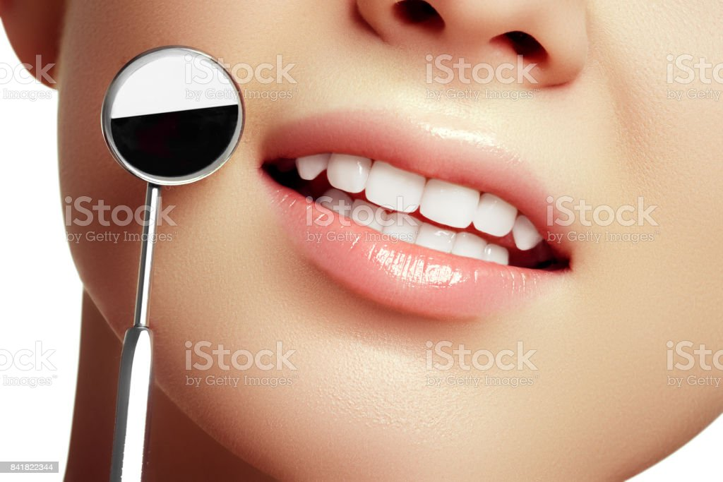 Healthy white woman teeth and a dentist mouth mirror closeup. Isolated on a white background. Dental hygiene, oral care concept - foto stock