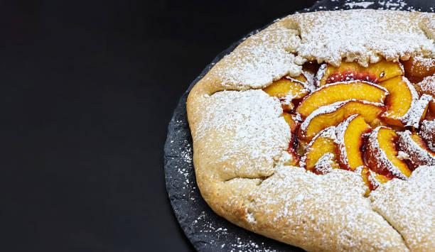 gesunde vollkorn-galette mit pfirsiche nektarinen. schwarzer hintergrund. kopieren sie raum. textbereich. - crostata stock-fotos und bilder