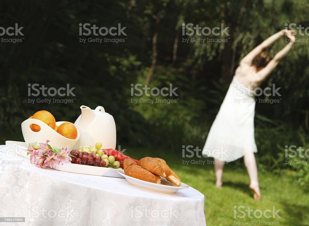 Healthy Woman Doing Yoga Before a Summer Outdoor Breakfast stock photo