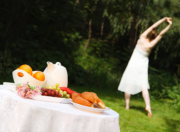 healthy woman doing yoga before a summer outdoor breakfast - carolinemaryan stock pictures, royalty-free photos & images