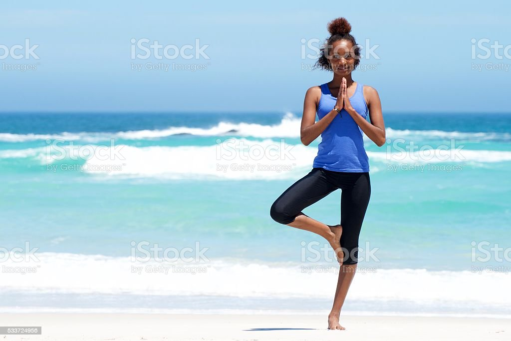 Healthy woman doing yoga exercise at beach stock photo