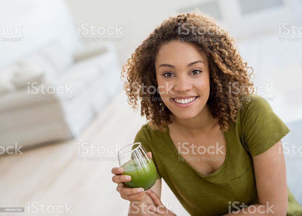 Healthy woman drinking an organic green juice stock photo