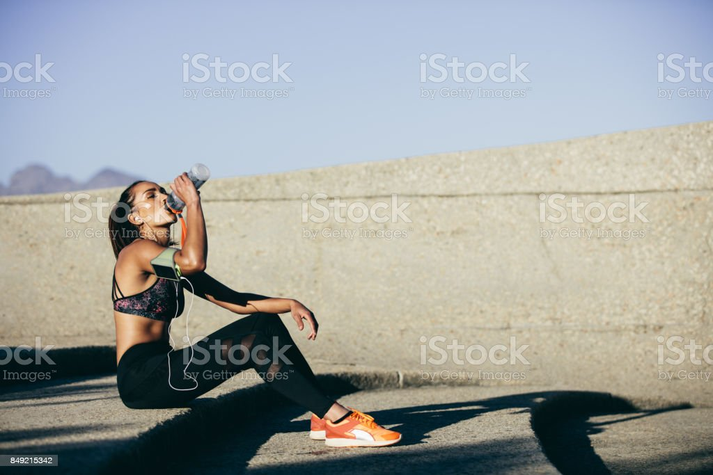 Healthy woman drinking water after exercising stock photo
