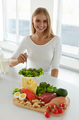 Healthy Nutrition. Beautiful Woman On Diet Eating Organic Green Vegetable Salad In Kitchen. Happy Smiling Girl Sitting At Table With Different Food Products And Ingredients. High Resolution