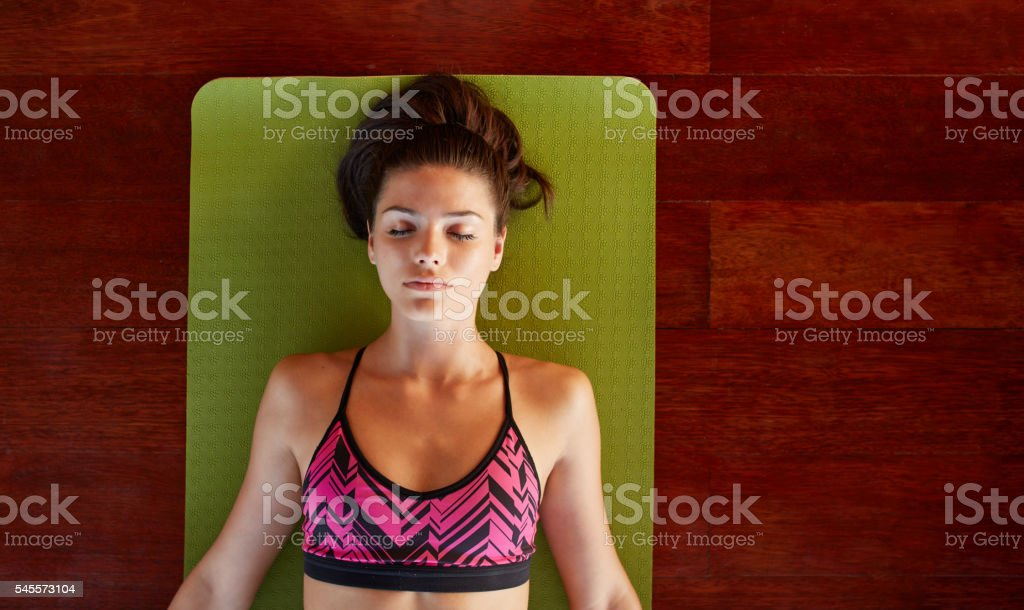 Healthy woman in savasana pose at gym stock photo