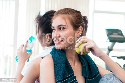istock Healthy woman is eating apple fruit in fitness gym 918238568