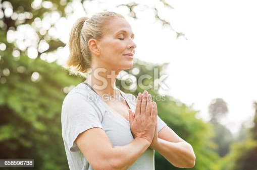 Mature woman in park joining hands with closed eyes and meditates. Relaxed senior woman with joined hands breath deeply with closed eyes. Healthy woman meditating outdoor.