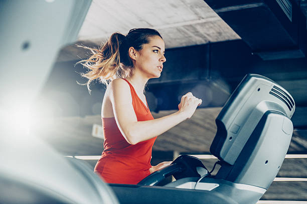 Healthy Woman Running on Treadmill Healthy young woman in GYM running on treadmill treadmill stock pictures, royalty-free photos & images