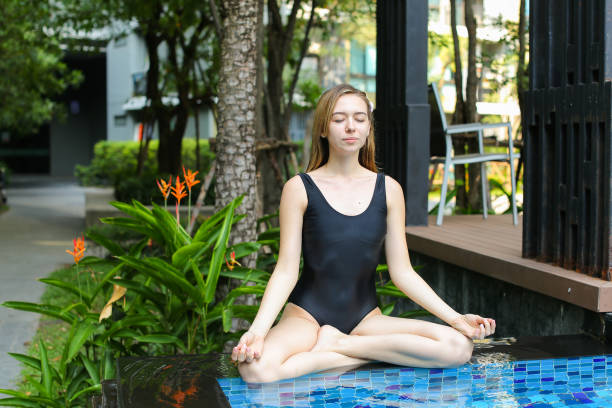 healthy woman sitting in lotus position, doing yoga by the pool - mulher natureza flores e piscina imagens e fotografias de stock