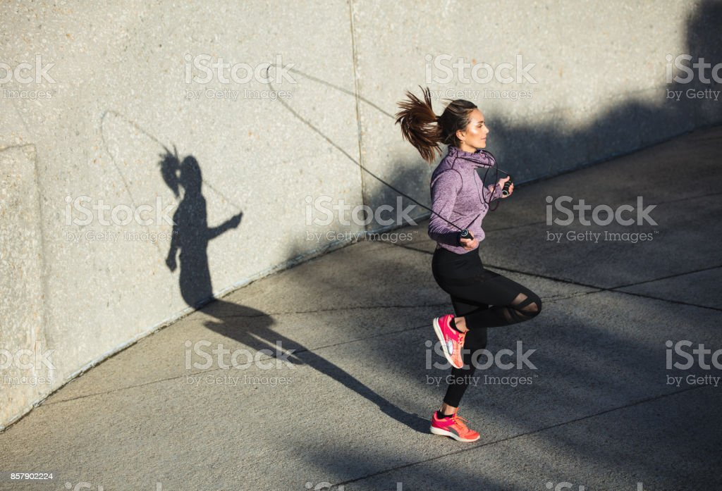 Healthy woman skipping ropes outdoors stock photo