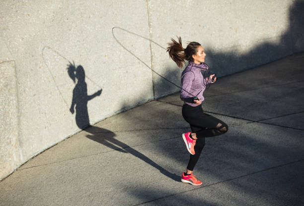 Healthy woman skipping ropes outdoors Fitness woman skipping with a jump rope outdoors. Female doing fitness training in morning. endurance stock pictures, royalty-free photos & images