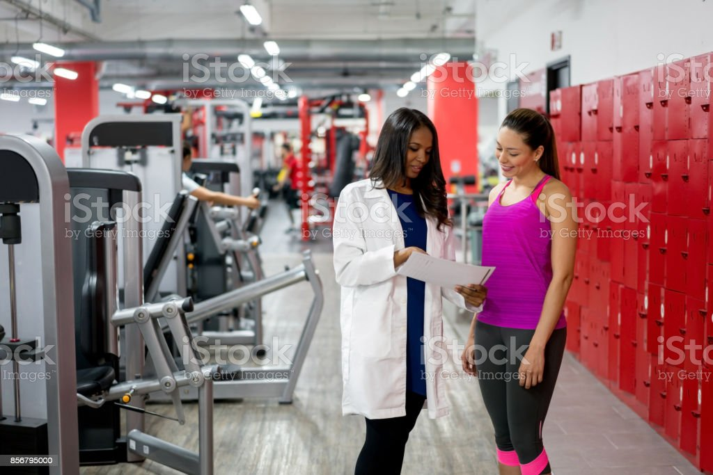 Healthy woman talking to the doctor at the gym stock photo