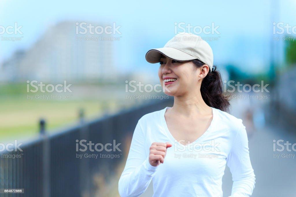 healthy woman walking outdoors stock photo
