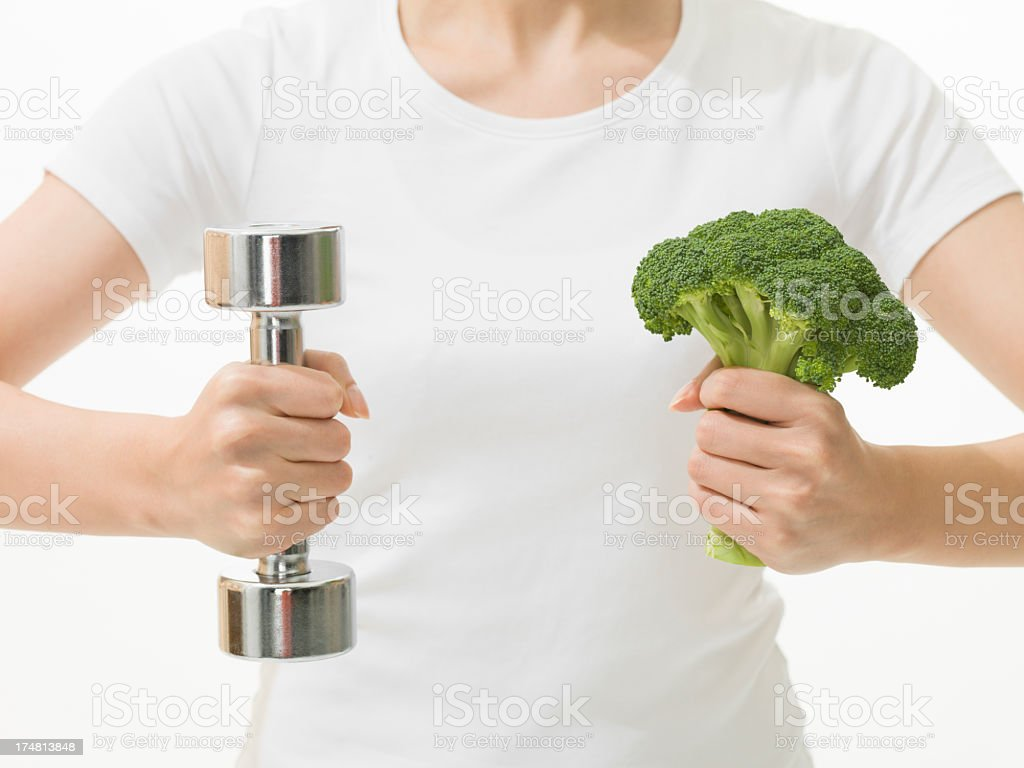 Healthy woman who grasps broccoli and dumbbell royalty-free stock photo