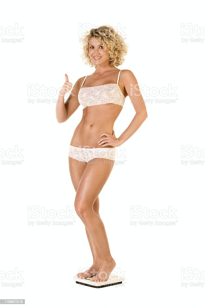 Healthy woman with perfect weight standing on scales royalty-free stock photo