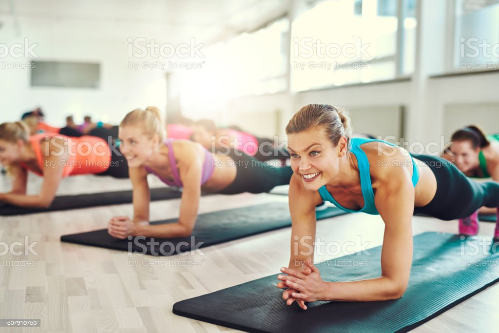 Healthy Women Doing Planking Exercise in Studio stock photo