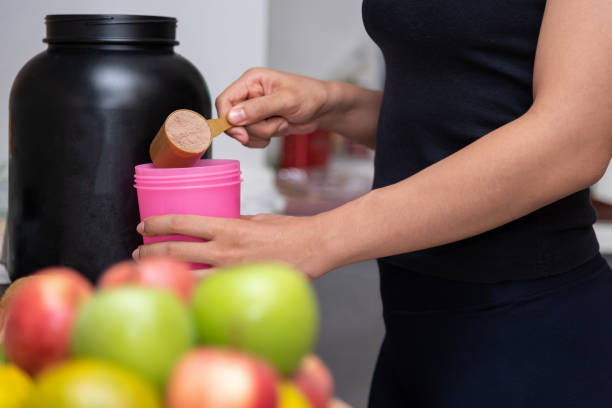 healthy women preparing a whey protein after doing weight training in the kitchen with fresh fruits as a blurred foreground. - protein stock photos and pictures