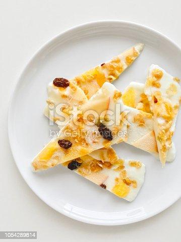 Homemade healthy frozen muesli yogurt bark with orange and apple, top view