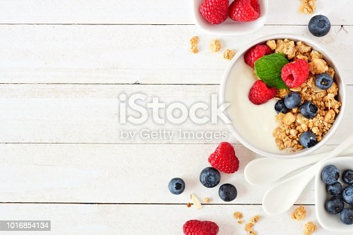 istock Healthy yogurt with berries and granola, side border over white wood 1016854134