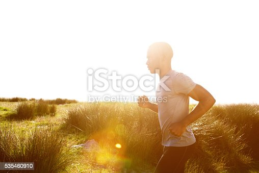 Side portrait of healthy young african man running at the beach with bright sunlight from back