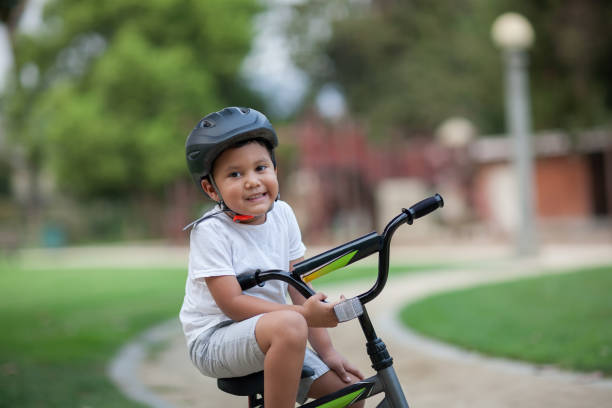 A healthy young boy sitting on his bike on a park trail who is wearing a safety helmet, t-shirt and shorts. stock photo