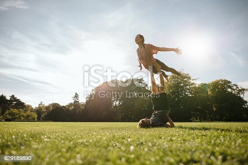 istock Healthy young couple doing acrobatic yoga at park 629189890