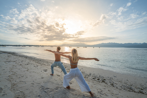 istock Healthy young couple exercising yoga outdoors on the beach at sunrise in a tropical climate, Bali, Indonesia. People healthy balance concept 1048603378