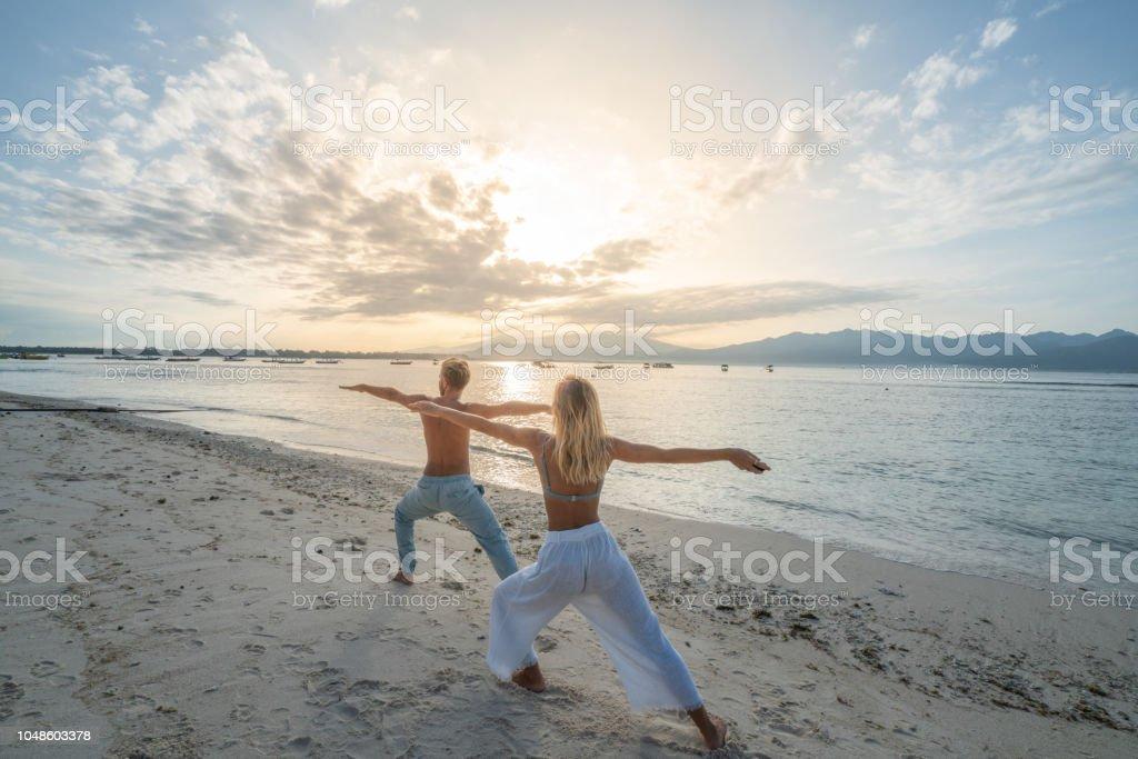 Gesunde junge Paar Ausübung von Yoga im freien am Strand bei Sonnenaufgang in einem tropischen Klima, Bali, Indonesien. Menschen gesunde Balance Konzept – Foto