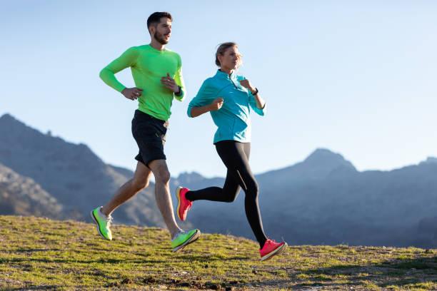 Gesundes junges Paar läuft morgens auf dem Bergweg. – Foto