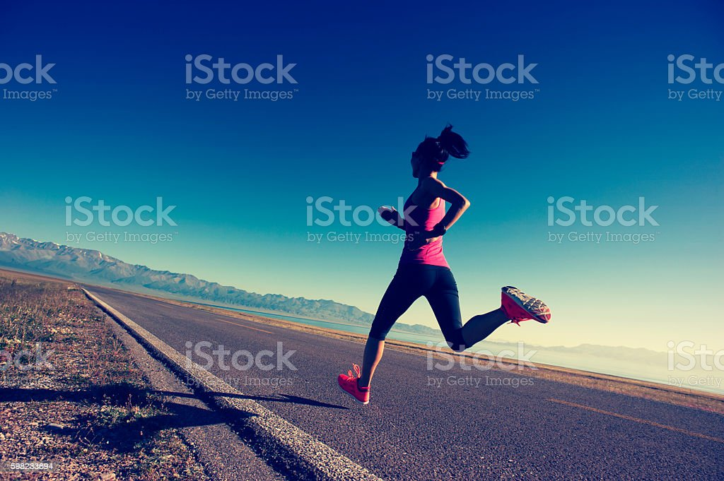 healthy young fitness woman runner running on sunrise seaside trail foto royalty-free