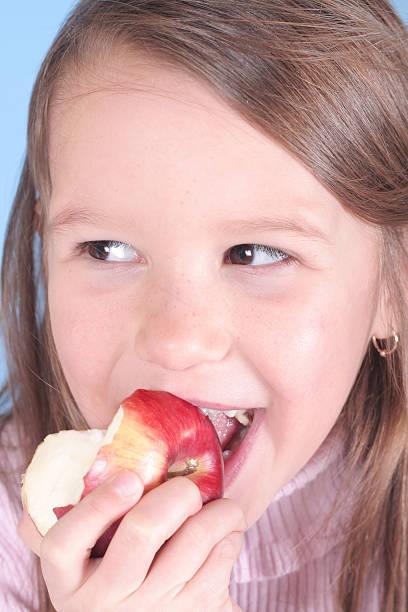 Healthy young girl eating apple stock photo