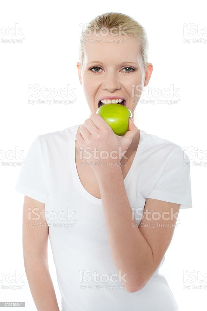 Healthy young girl eating nutritious green apple stock photo