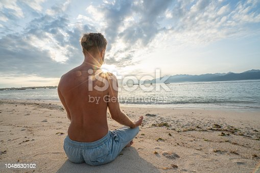 Healthy young man exercising yoga outdoors on the beach at sunrise in a tropical climate, Bali, Indonesia. People healthy balance concept