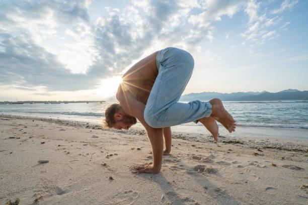 Gesunde junge Mann Ausübung von Yoga-Krähe-Pose im freien am Strand bei Sonnenaufgang in einem tropischen Klima, Bali, Indonesien. Menschen gesunde Balance Konzept – Foto